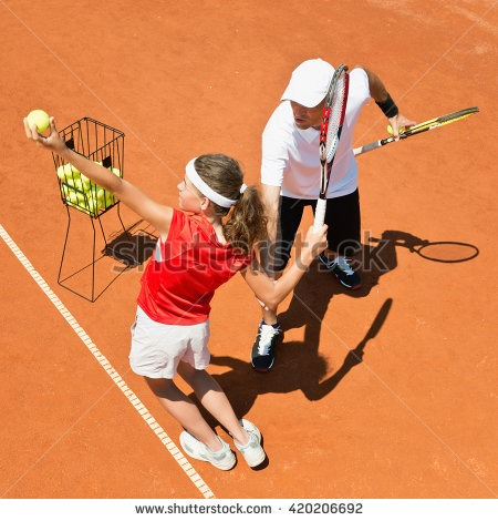 stock-photo-junior-tennis-player-practicing-serving-with-coach-420206692