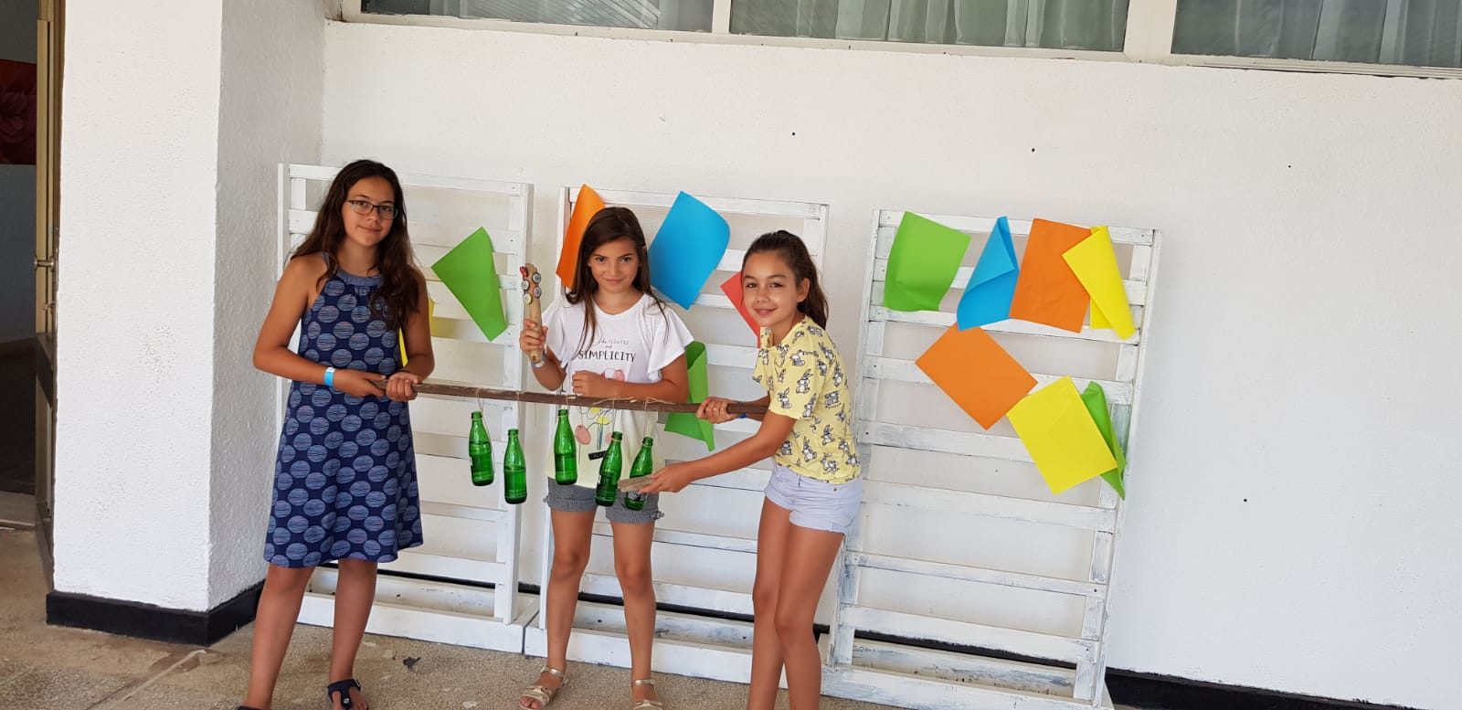 Z camp, Day 14 - music workshop - 3 girls show a hand-made musical instrument from tied, hanging, glass bottles