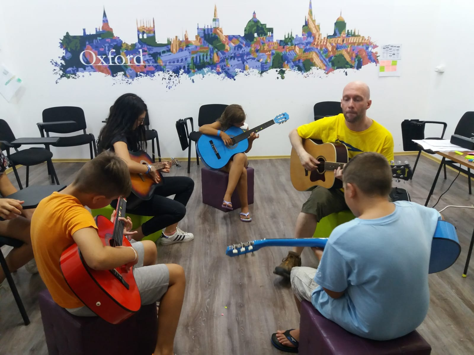 Z camp, Day 14 - music workshop - teacher, 2 girls and 2 boys, each with a guitar playing