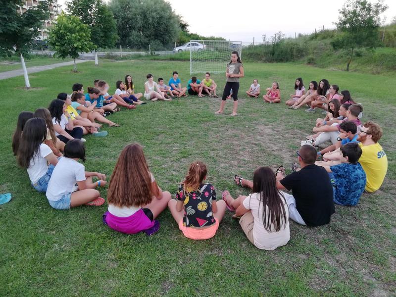 Z кемп, ден 1, децата седят в кръг на тревата за встъпителните думи на част от екипа на Зенира