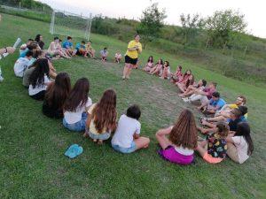 Z кемп, ден 1, децата седят в кръг на тревата за встъпителните думи на екипа на Зенира