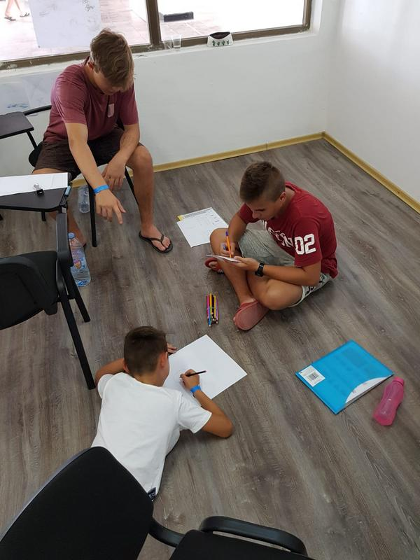 Z кемп, ден 3, момчета пишат в час по английски език седнали на земята