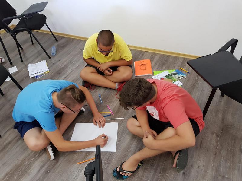 Z кемп, ден 3, час по английски език, момчета пишат седнали на земята