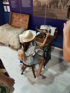 Z кемп, ден 10 - музеят в Царево, момиче седи пред стара, шевна машина