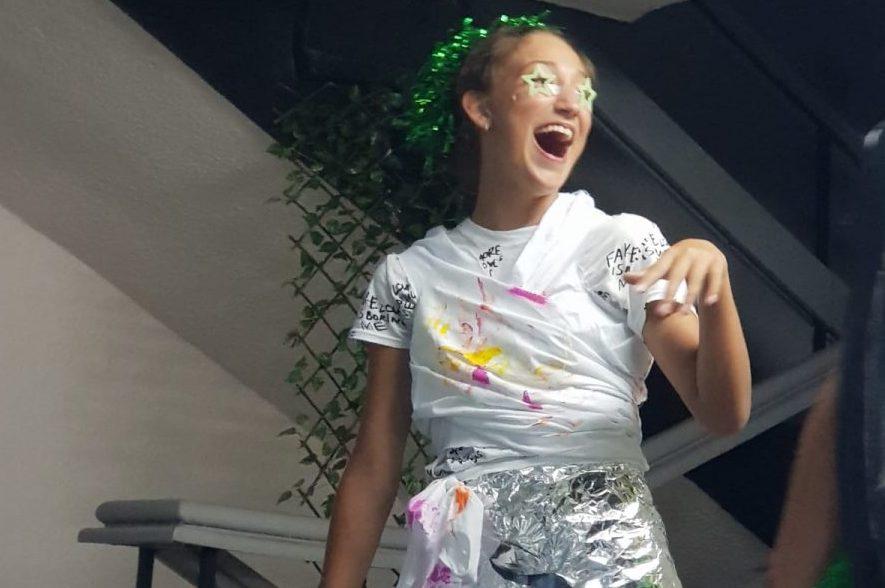 Z кемп, ден 11 - модно шоу космос, момиче с пола от метално фолио, гримирано с бели очи и зелен венец на главата
