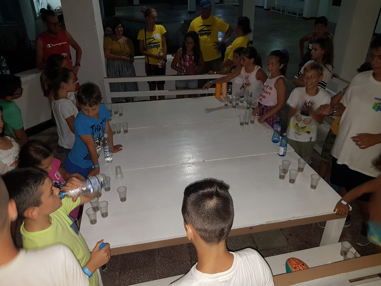 Z camp, Day 13 - Z Disco, children and teachers are gathered around a table and drink juice and water