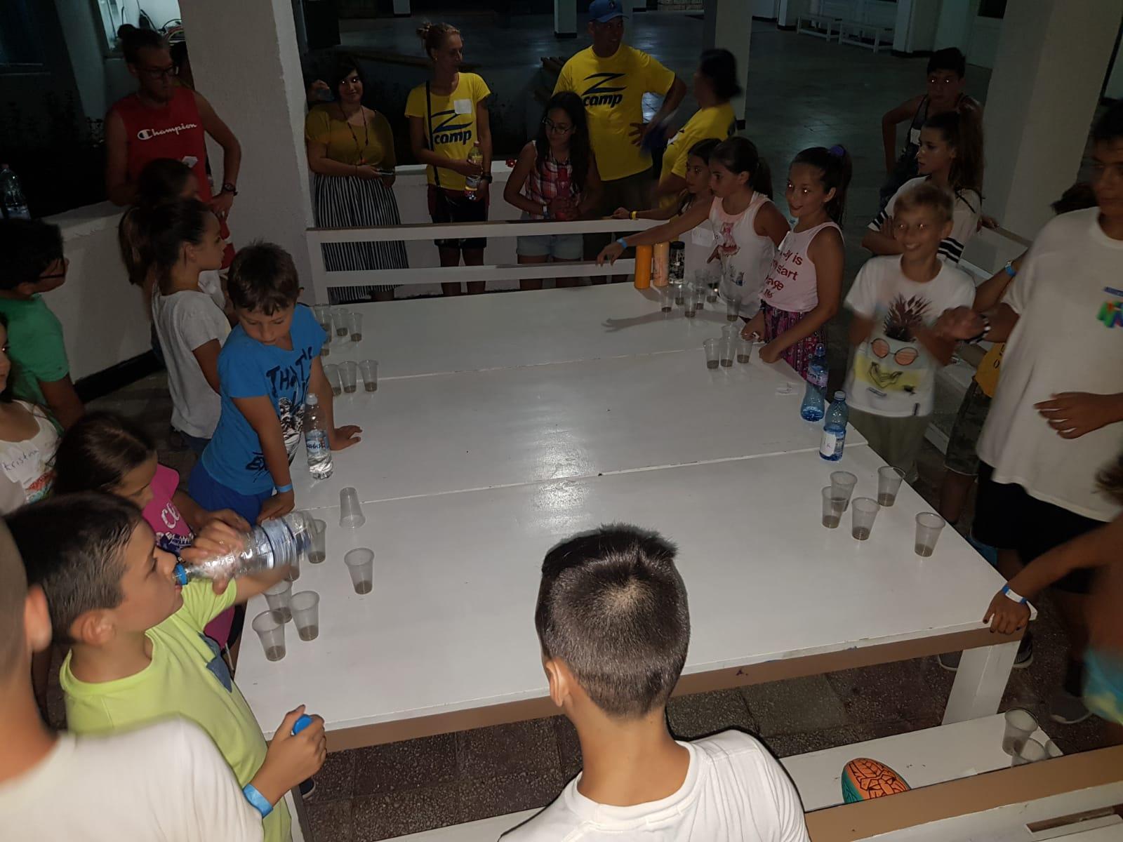 Z кемп, Ден 13 - Z Диско, децата и учителите са събрани около маса и пият сок и вода