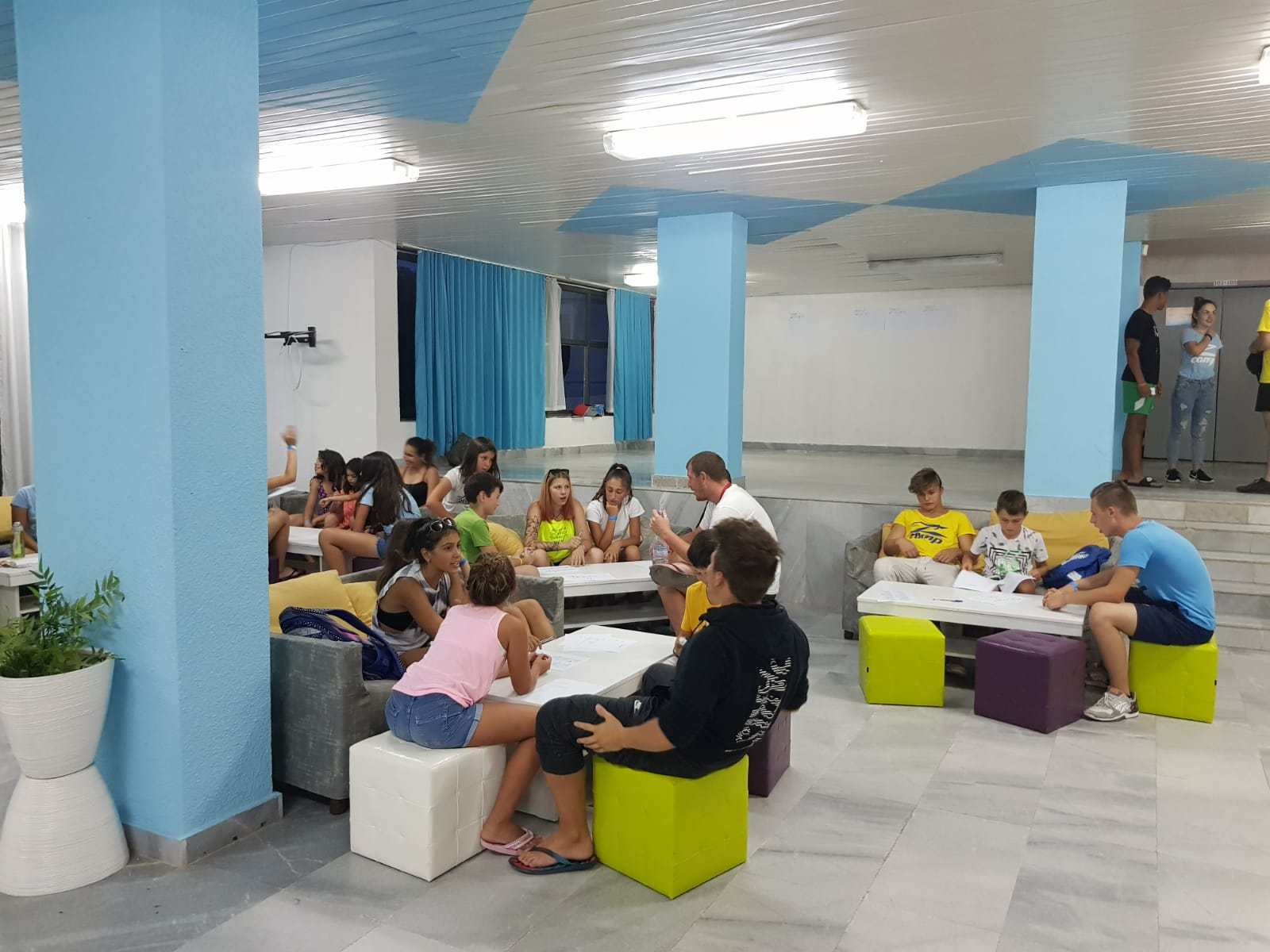 Z camp, day 7 - teams of children discuss the game in the lobby