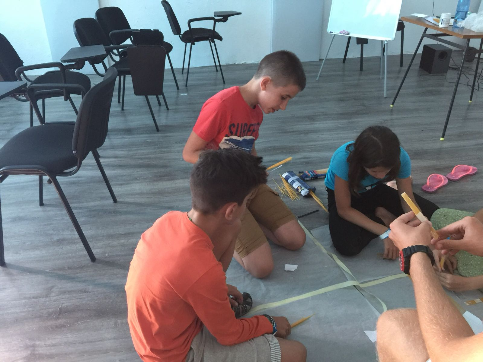 language camps for kids at Bulgarian seaside Z camp, Day 28 - arts&crafts - three children sitting on the ground building a bridge of spaghetti and tape