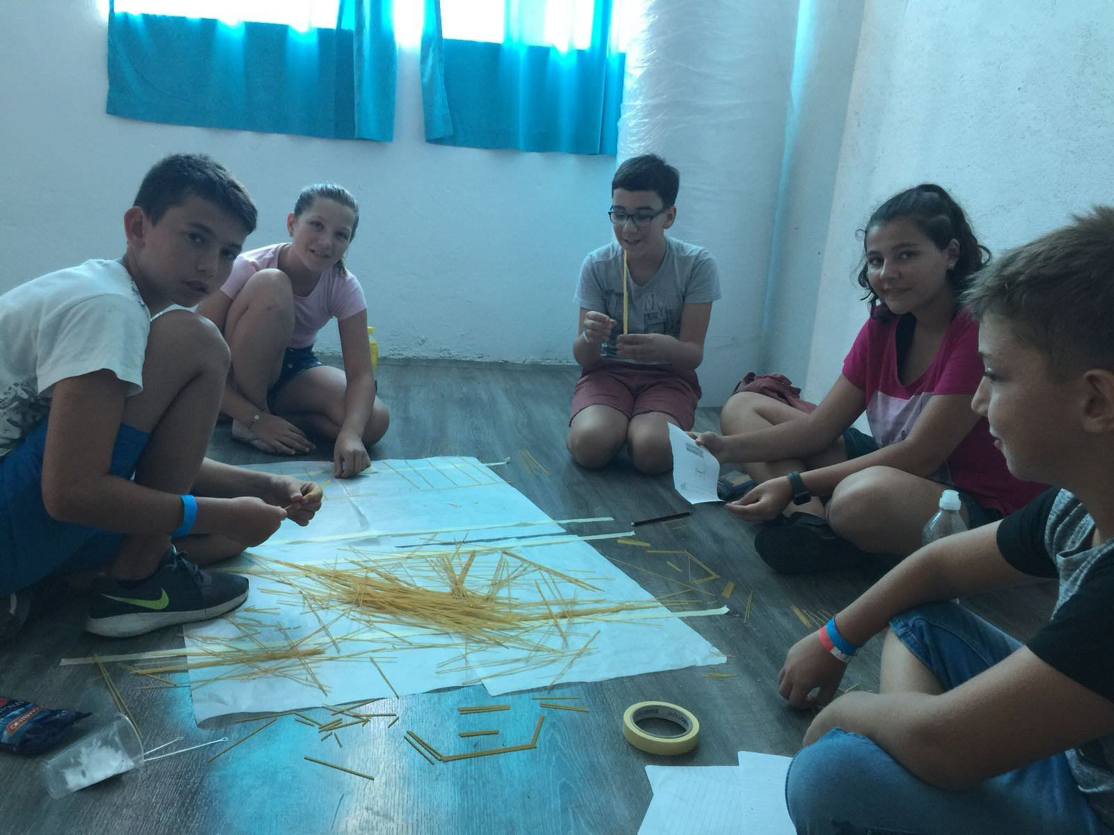 language camps for kids at Bulgarian seaside Z camp, Day 28 - arts&crafts - five children sitting on the ground building a bridge of spaghetti and tape