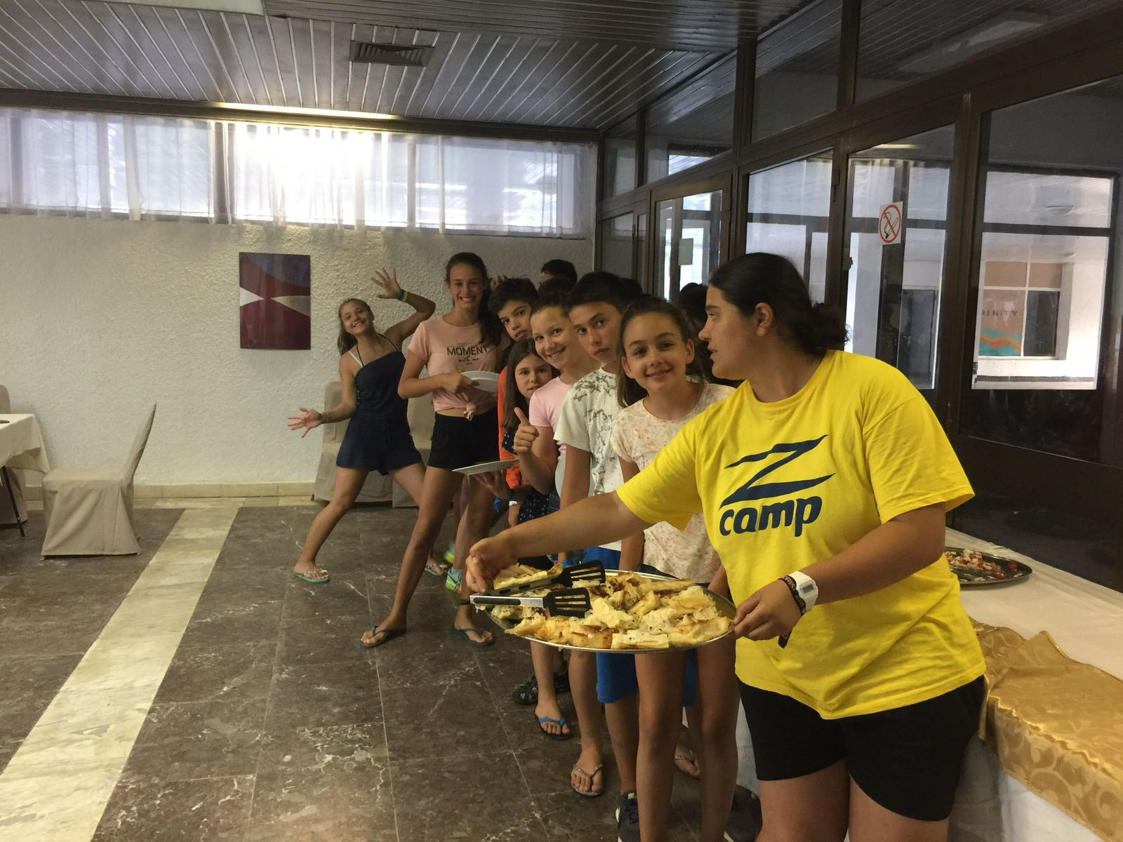 language camps for kids at Bulgarian seaside Z camp, Day28 - cooking - photo of the group with a tray with bells