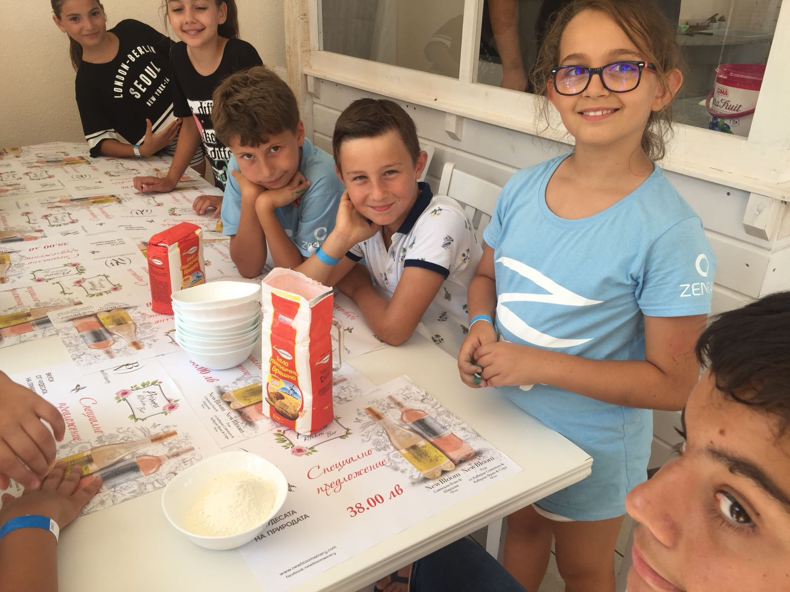 Z camp, day 14 - cookingworkshop, making pizza, a group of kids around the table prepared with flour for the dough