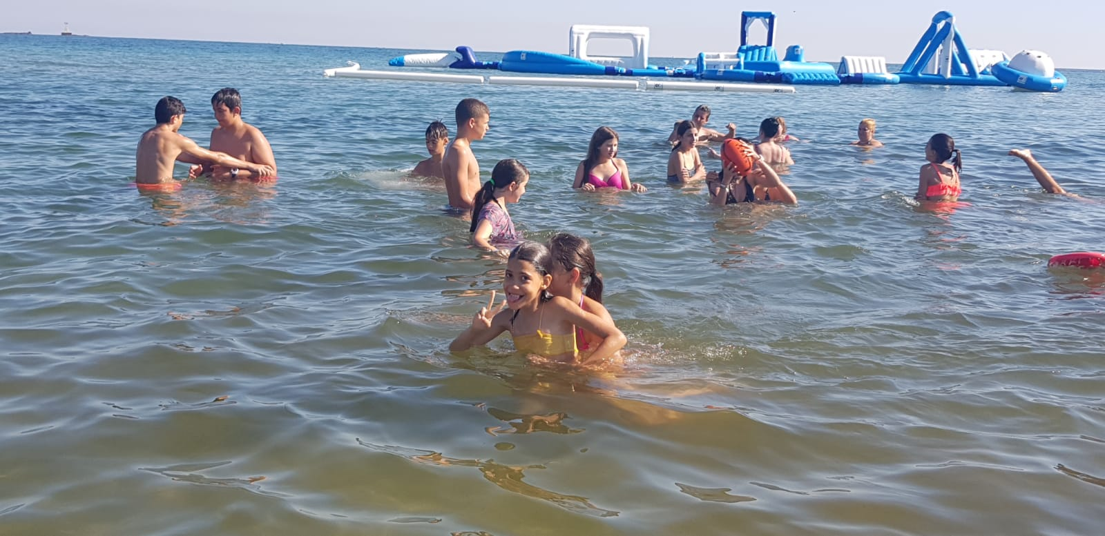 Language Camp for kids Bulgarian Seaside Z camp, Day 21 - at the beach - children bathe in the sea, behind them an inflatable water attraction