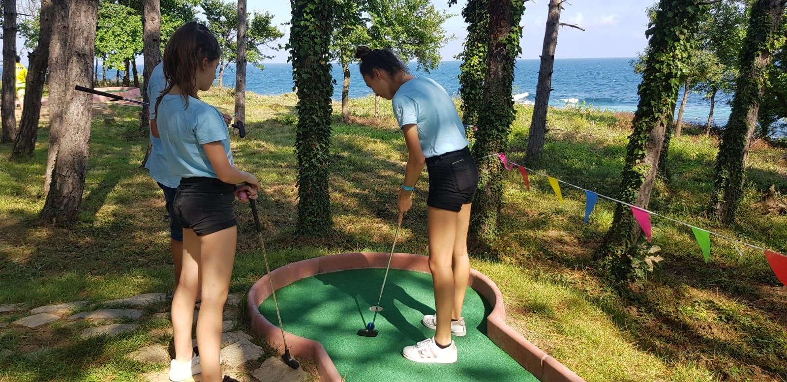 Z кемп, ден 19 - мини голф в Царево - 3 деца с фланелки на Z camp са при игрището срещу морето