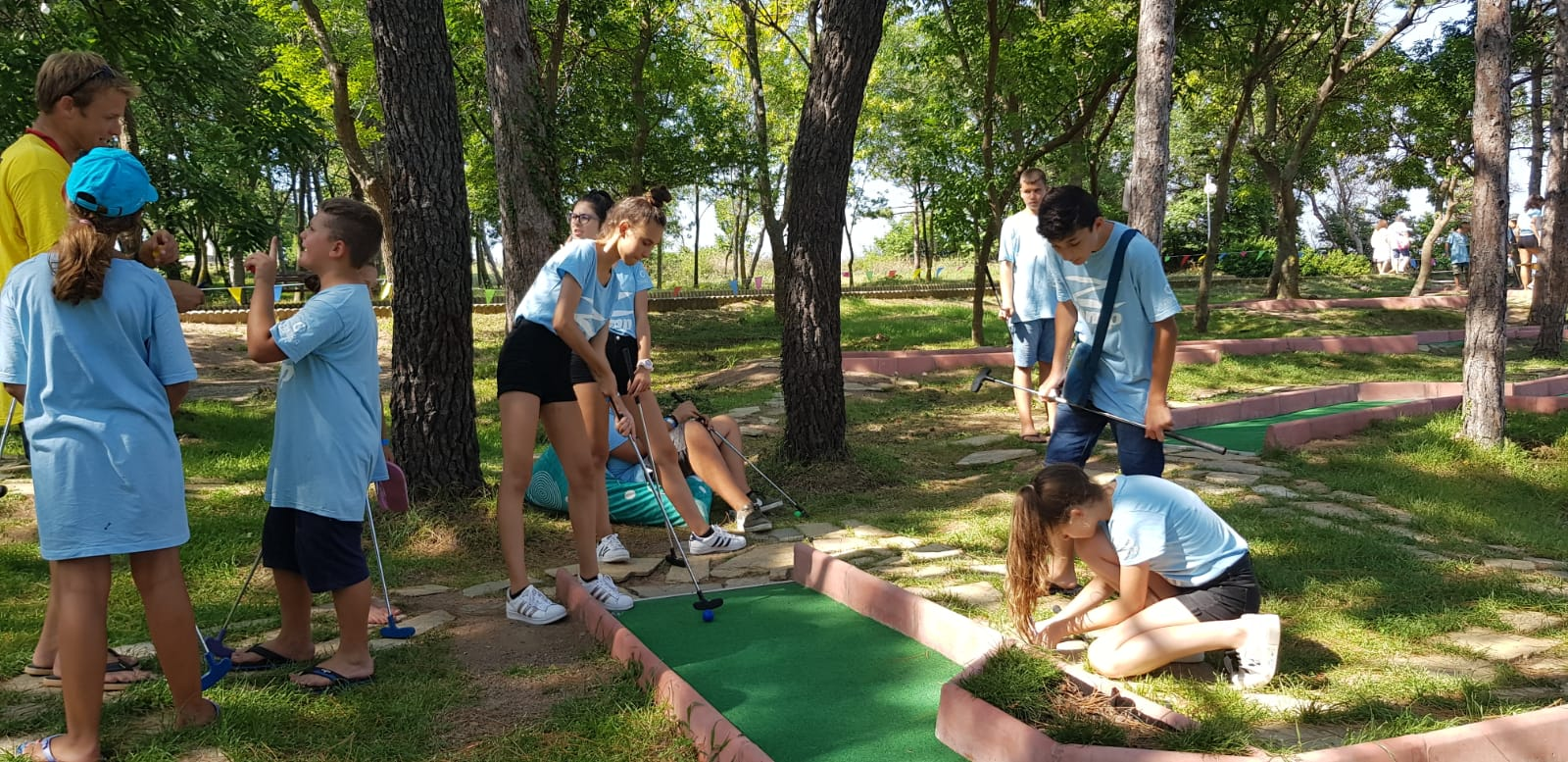 Z camp, day 19 - mini golf in Tsarevo - group of children with blue T-shirt of Z camp and girl aiming at the ball