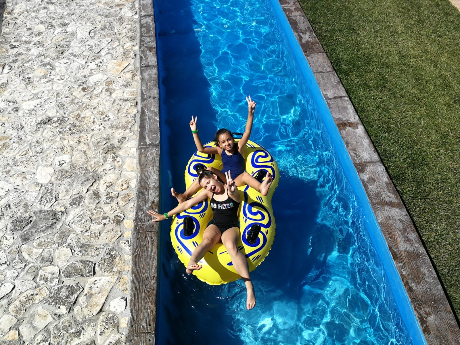 Language Camp for Kids Z camp, Day 23 - aqua park Neptune - two girls sitting in a large belt are floating along river