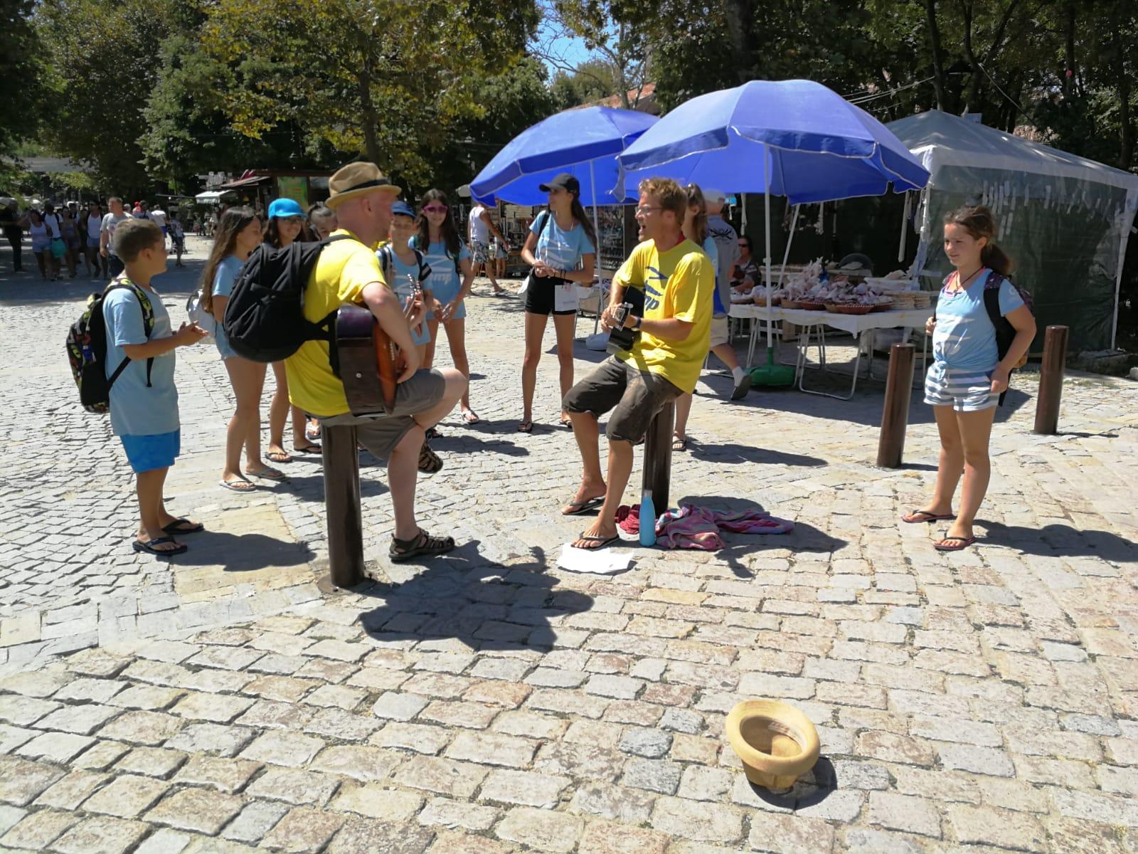 езиков лагер за деца Z кемп, Ден 23 - разходка до Созопол - двама учители с китари и децата в стария град