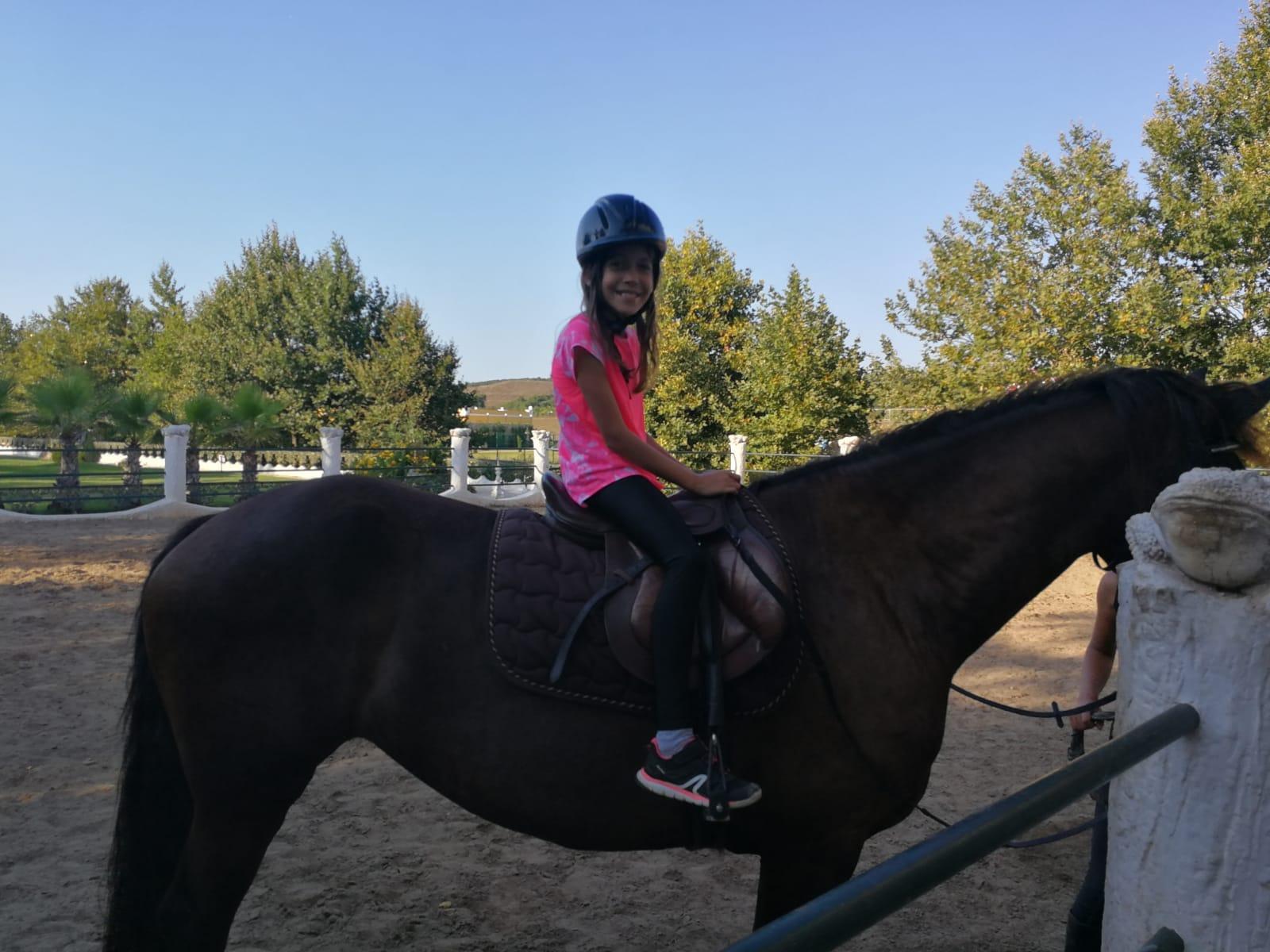 езиков лагер за деца Z кемп, Ден 23 - конна езда - момиче с каска седи върху кон