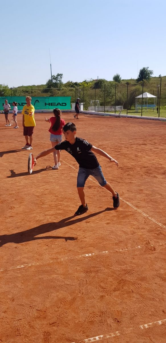 Z camp, day 20 - tennis court - boy with black t-shirt, denim shorts, black sneakers, prepares to hit the ball