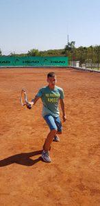 Z кемп, ден 20 - тенис корт - момче със сини фланелка, къси панталони, маратонки, замахва за удар