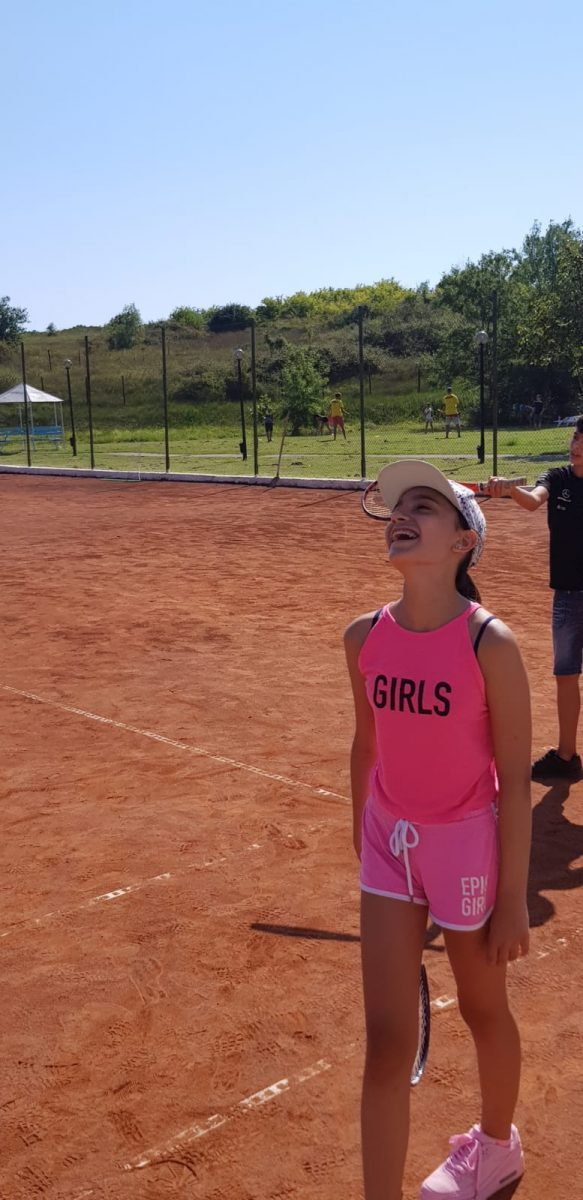 Z camp, Day 20 - tennis court - girl with white hat and pink top, pants and sneakers, rocket in hand