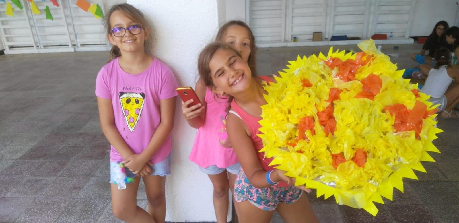 Z camp, Day 20 - Arts and crafts - 3 girls in pink with a paper bouquet of yellow flowers