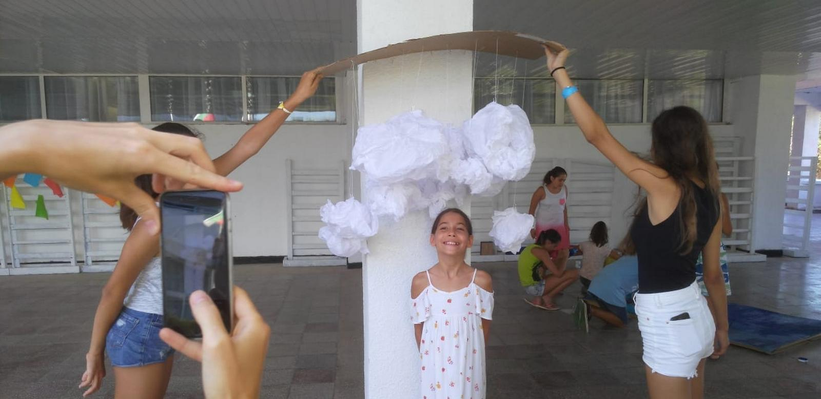 Z camp, Day 20 - Artс and crafts - a little girl with hanging, paper clouds above the head