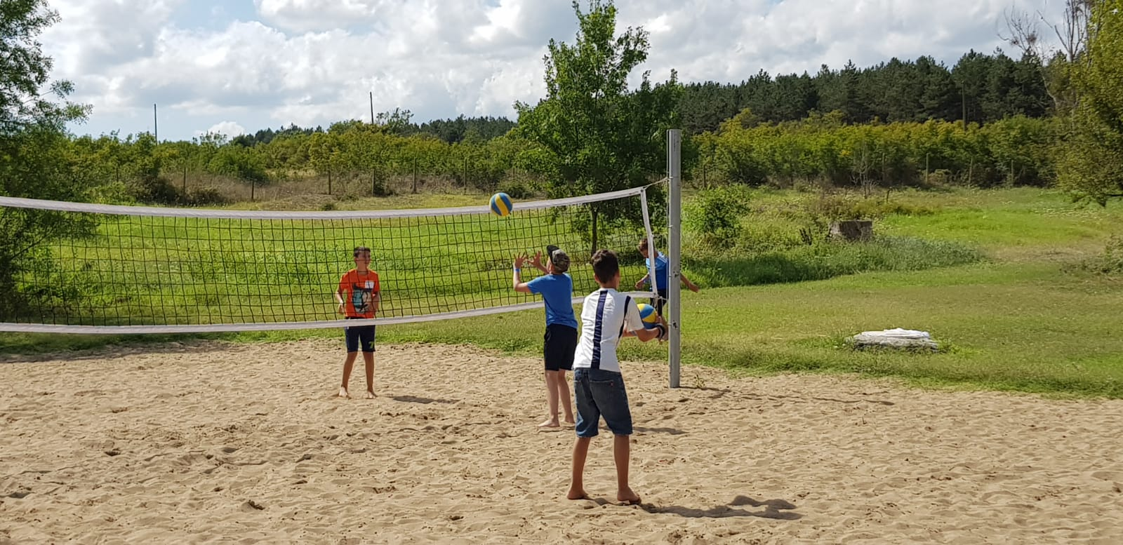 language vacations for kids at Bulgarian seaside Z camp, Day 27 - volleyball court - three guys play