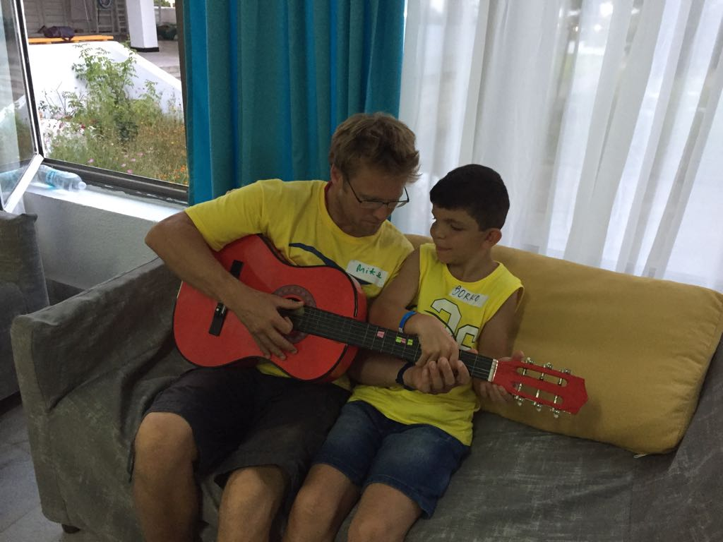 language vacations for kids at Bulgarian seaside Z camp, Day 27 - musical workshop - teacher teaches a boy to play guitar