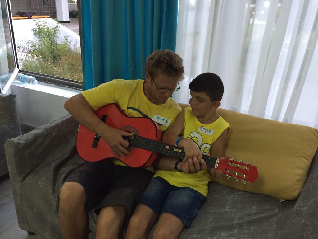 езикови ваканции за деца в България на море Z кемп, Ден 27 - музикална работилница - учител учи момче да свири на китара