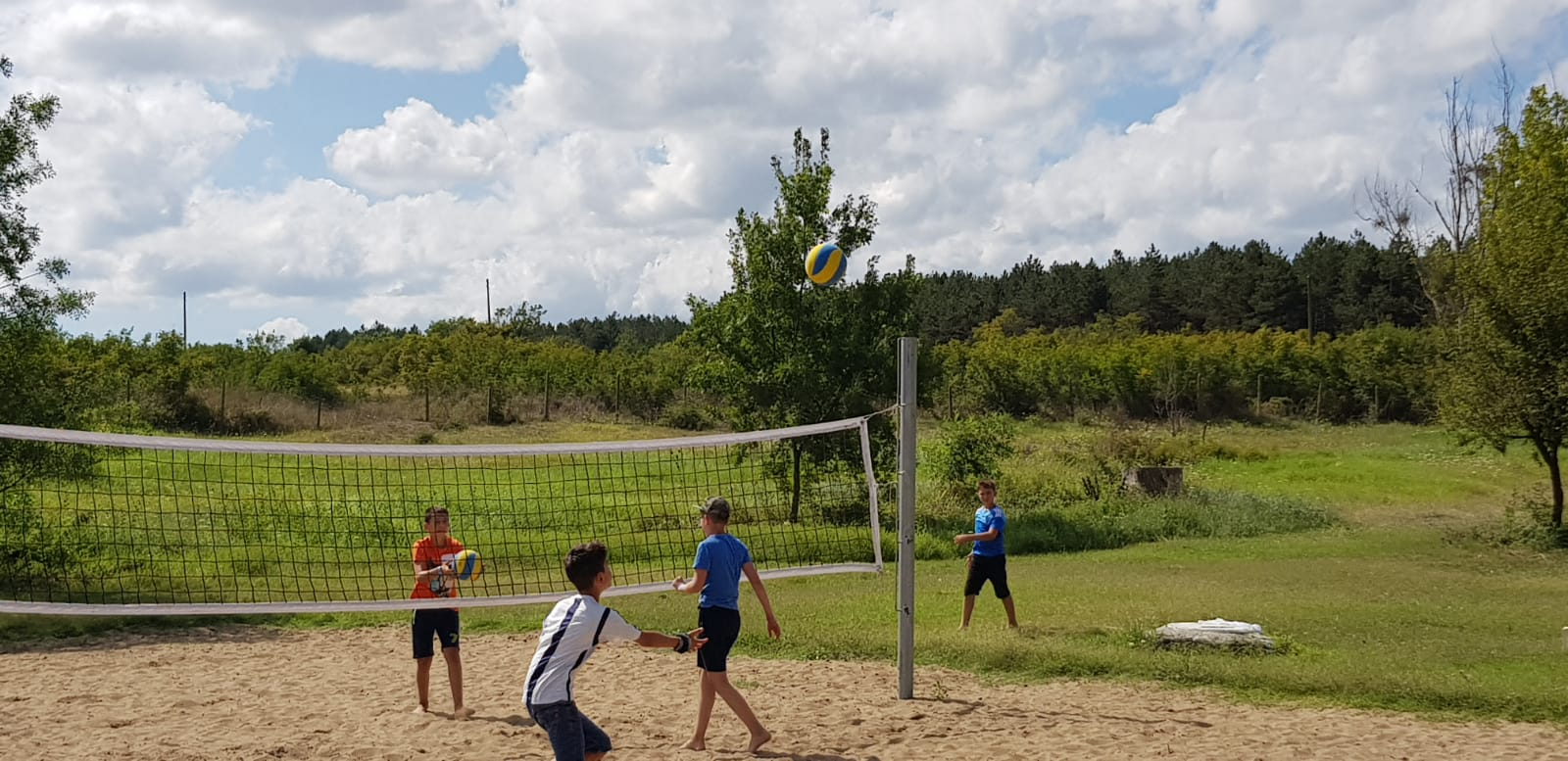 language vacations for kids at Bulgarian seaside Z camp, Day 27 - volleyball court - boy prepares to hit the ball