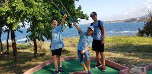 езикови ваканции в България за деца Z кемп, ден 32 - мини голф - 3 момчета са вдигнали стикове във въздуха