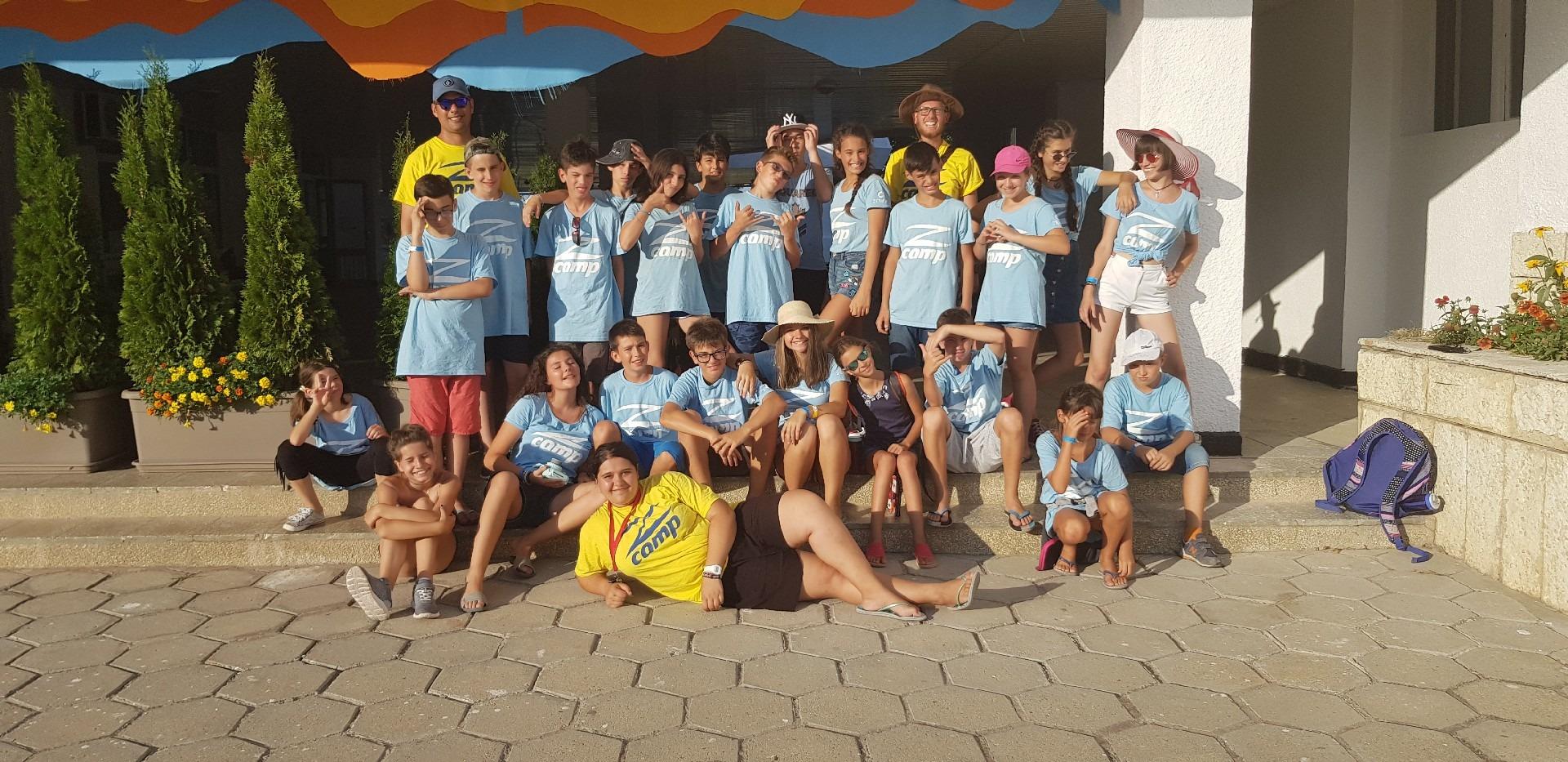 езикови ваканции в България за деца Z кемп, ден 32 - снимка на групата, децата са със сини фланелки с лого Z camp, учителите - жълти
