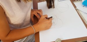 летни езикови лагери за деца Z кемп, ден 31 - сутрешен клас по англойски език, момиче рисува плакат