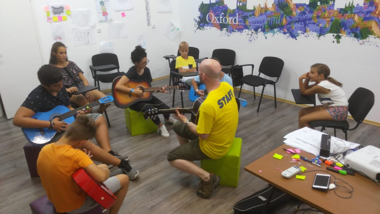 Z camp, Day 16 - music workshop - teacher and 4 children, each with guitar playing, others watching and listening