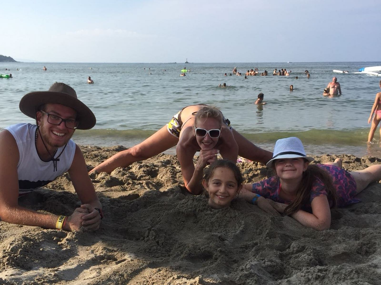Z кемп, ден 16 - на плажа, дете заровено до главата в пясъка и други около него, морето е на заден план