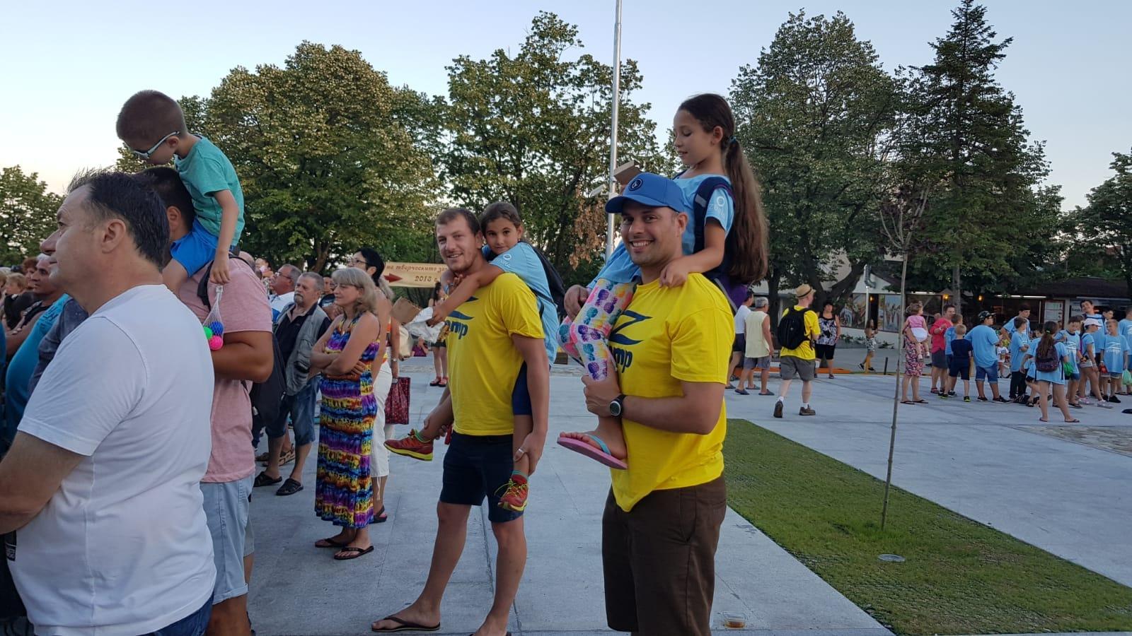Z кемп, ден 15 - фестивала на музиката и меда в Царево, двама учители с две момиченца на гърбовете им, наблюдават представление