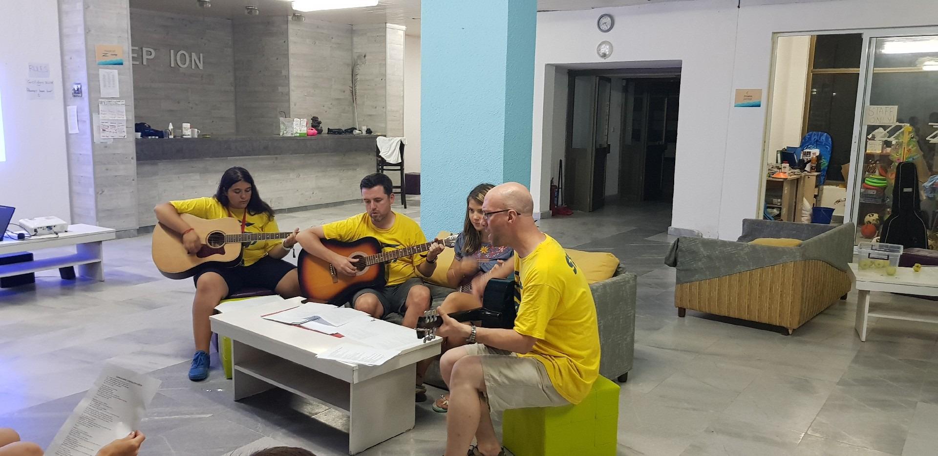 летни езикови лагери за деца Z кемп, Ден 37 - шоу на талантите - трима учители свирят на китари, едно момиче на укулеле