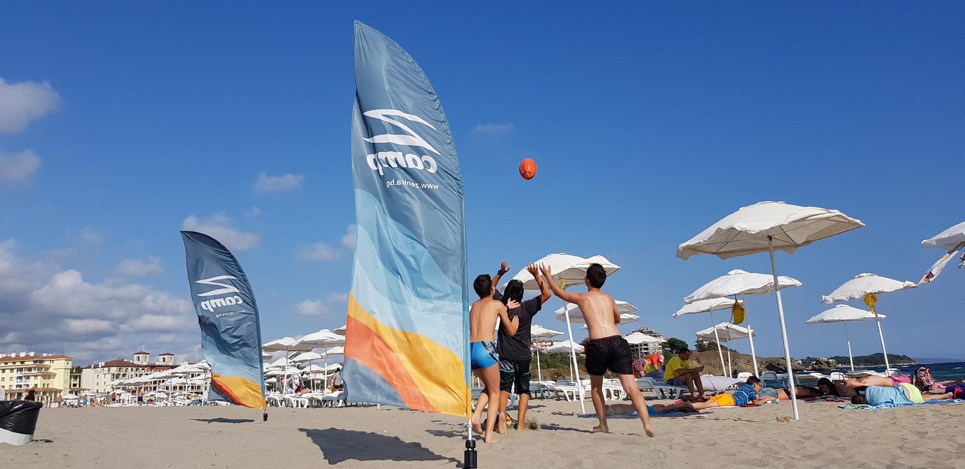 летни езикови лагери за деца Z кемп, Ден 37 - на плажа - три момчета играят с топка, до тях знамето на лагера Z camp