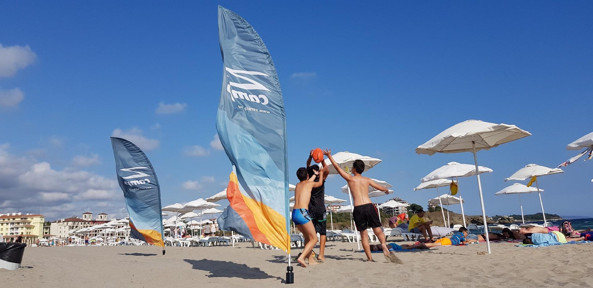 летни езикови лагери за деца Z кемп, Ден 37 - на плажа - три момчета хващат топката, до тях знамето на лагера Z camp