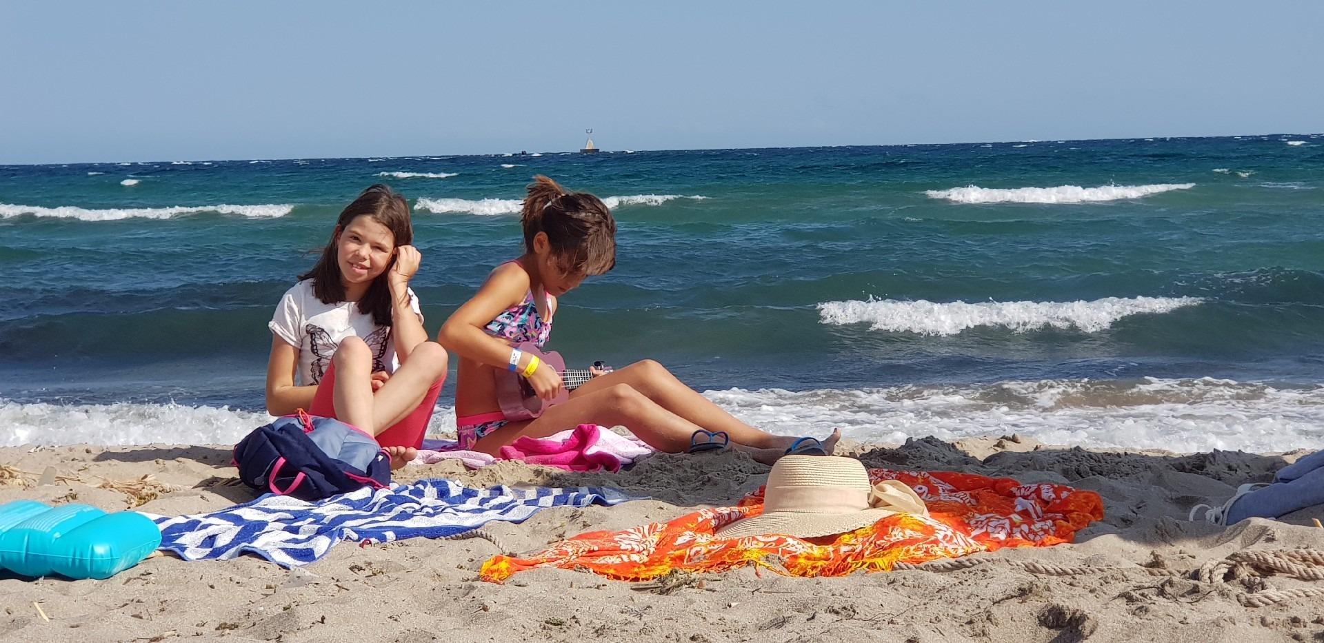 летни езикови лагери за деца Z кемп, Ден 37 - на плажа - две момичета седят на плажа, зад тях море