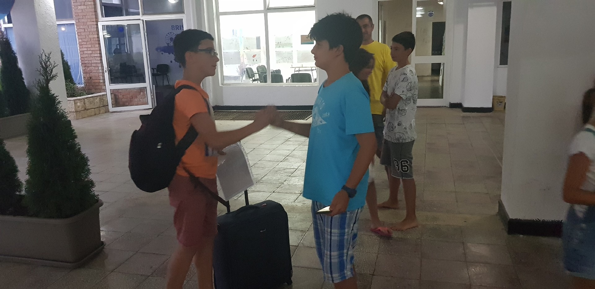 summer language camps for children Z camp, Day 38 - last evening - a boy with a briefcase farewell to another boy